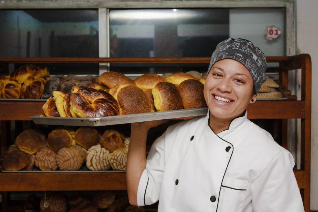 Empresaria inmigrantes: dueña de panadería sonriente cargando una bandeja de productos recién horneados. Concepto: préstamos para inmigrantes.