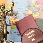 Statue, magnifying glass, passport and world map. Concept: immigration help, legal resources