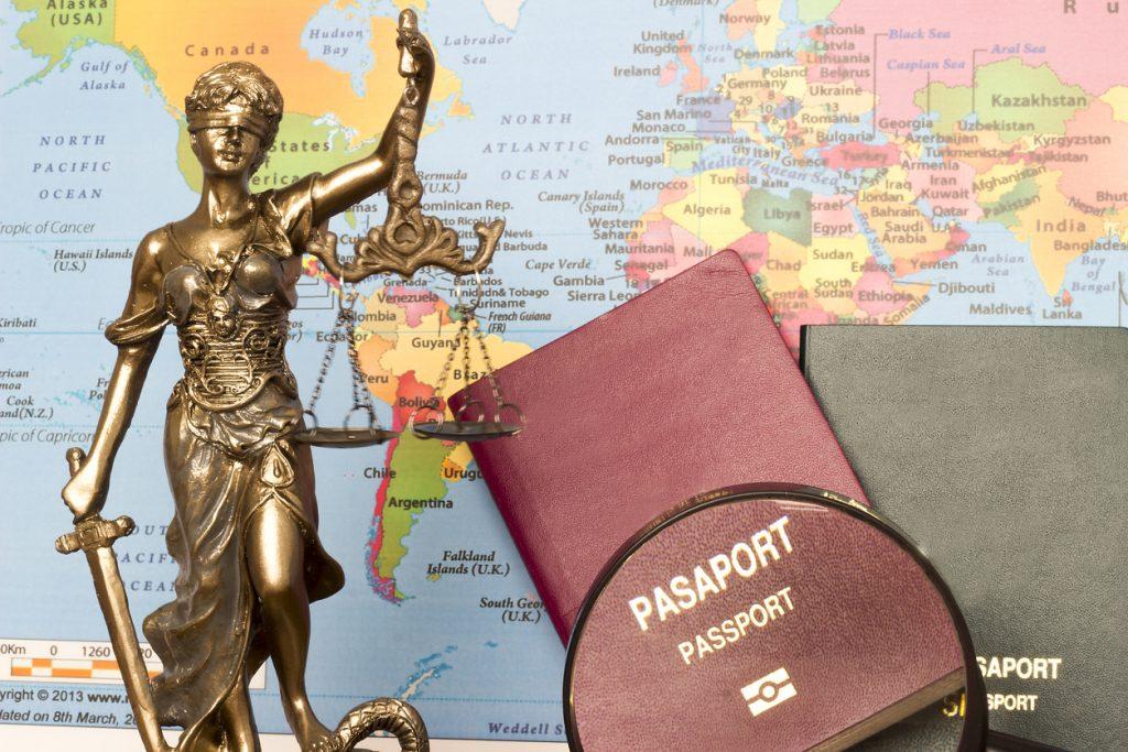 Estatua de la justicia, pasaportrs y lupa con fonde de mapa mundial. Concepto: ayuda para inmigrantes: recursos legales