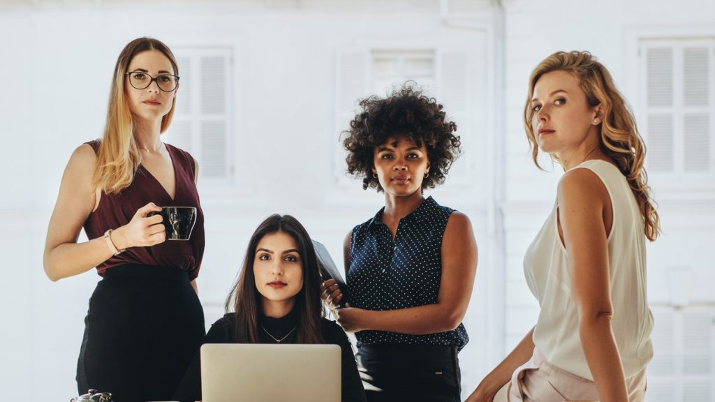 Group of multiracial businesswomen in casuals together at office desk and looking at camera. Female startup business team portrait. concept: mompreneur