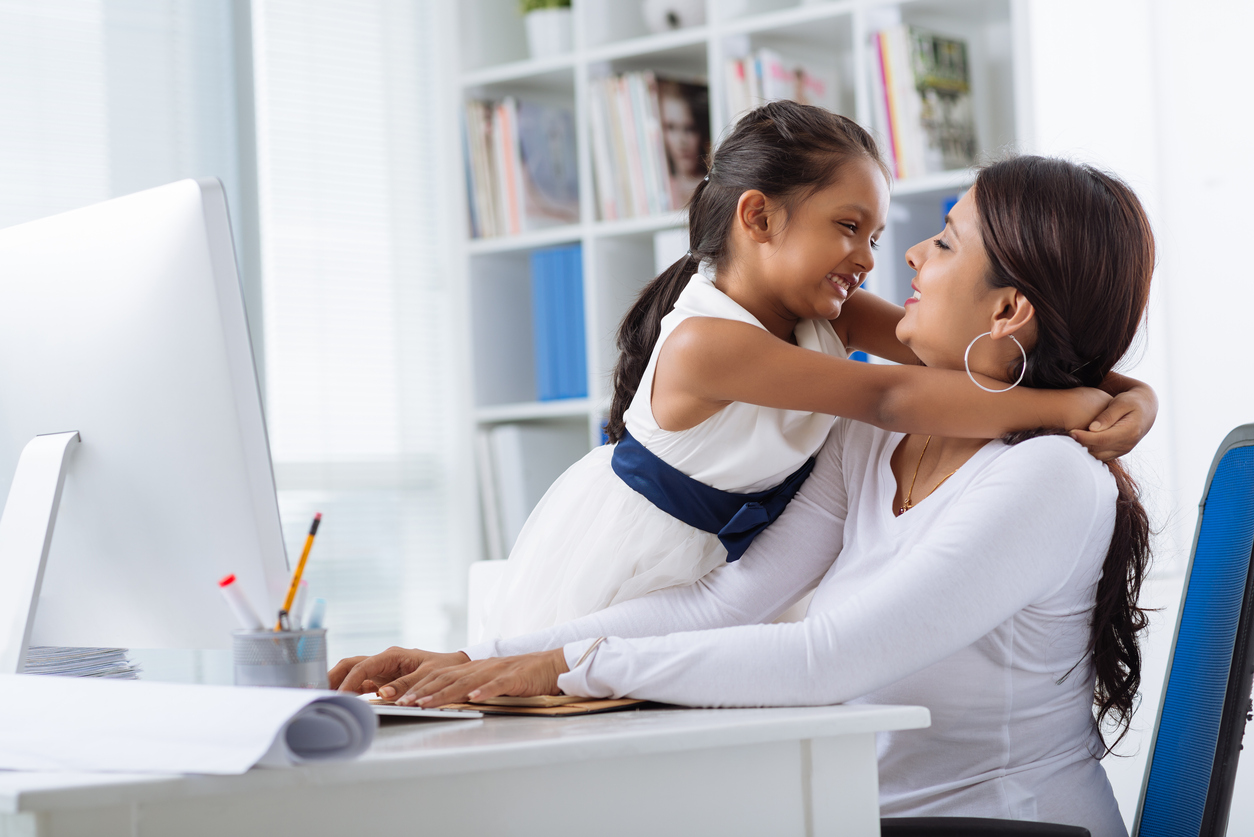 Young daughter embracing her mompreneur while she sitting at office desk and working on project