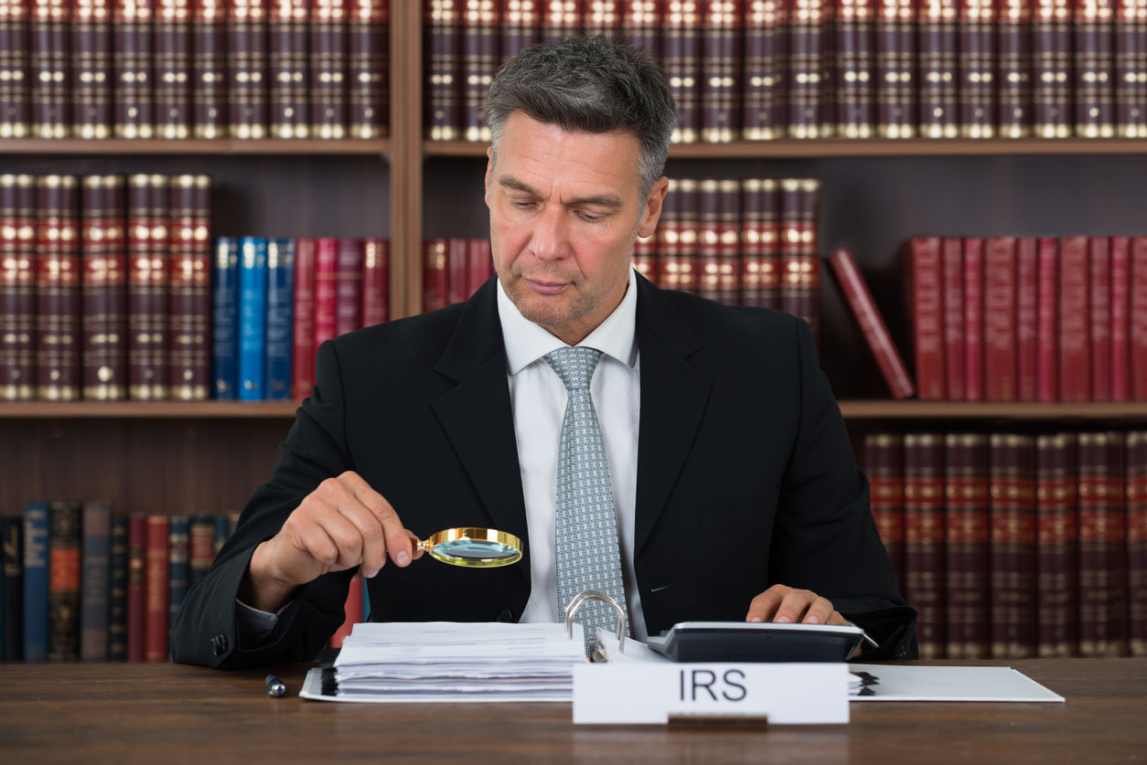 Mature male tax auditor examining documents with magnifying glass at table in office. Concept: IRS audit