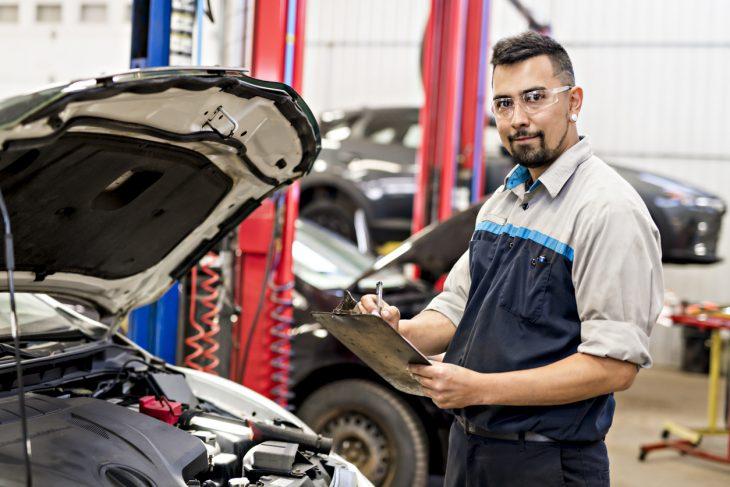 Mechanic worker in uniform working on car. Concept: equipment financing