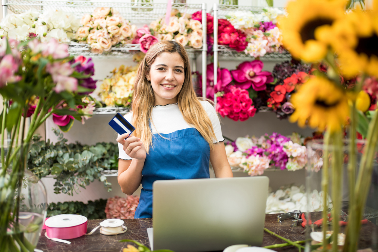 Flower shop owner holding a credit card next to a laptop computer in her flower shop and smiling. Concept: zero interest credit cards