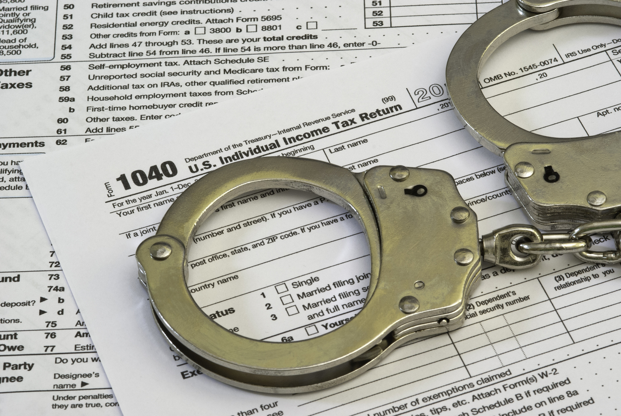 A 1040 income tax form with handcuffs on top.Concept: tax evasion and tax fraud.