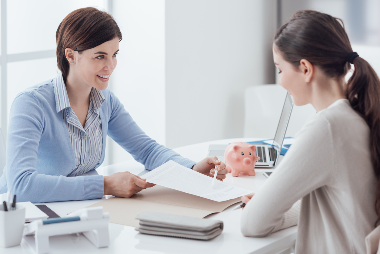 Profesional de impuestos y cliente reunidas en una oficina, y revisando documentos relacionados con impuestos. Concepto: dónde preparar impuestos
