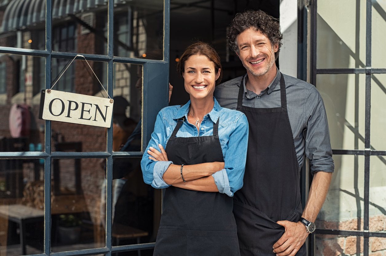 Couple of small business owners smiling and looking at camera while standing at business entrance door with open sign board. Concept: business license