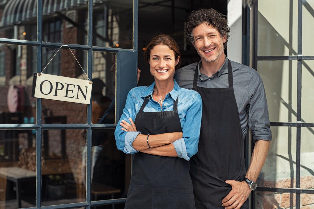 """Pareja de empresarios sonrientes en la puerta de su negocio con el cartel de """"abierto"""". Concepto: licencia comercial."""