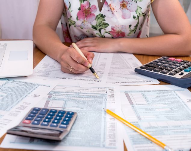 Woman filling 1040 individual tax form at workplace. Concept: tax deductions