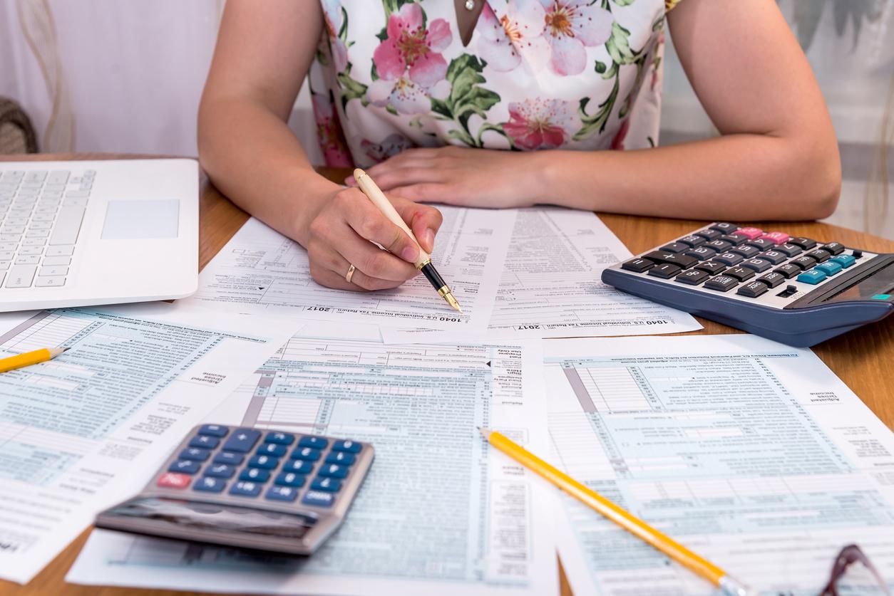 Mujer rellenando formulario 1040 sobre escritorio. Concepto: deducibles de impuestos.