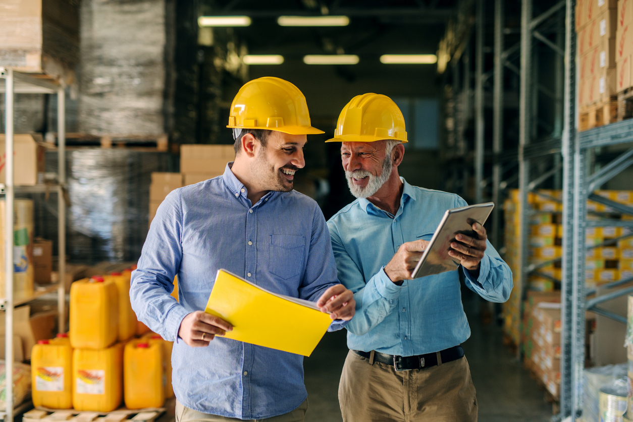 Padre e hijo en almacén llevando cascos de protección. El padre está enseñando algo en una tablet y el hijo lleva documentos. Concepto; pedir prestado a la familia