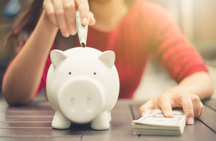 woman hand putting money bank note dollar into piggy for saving money. Concept: debs vs equity