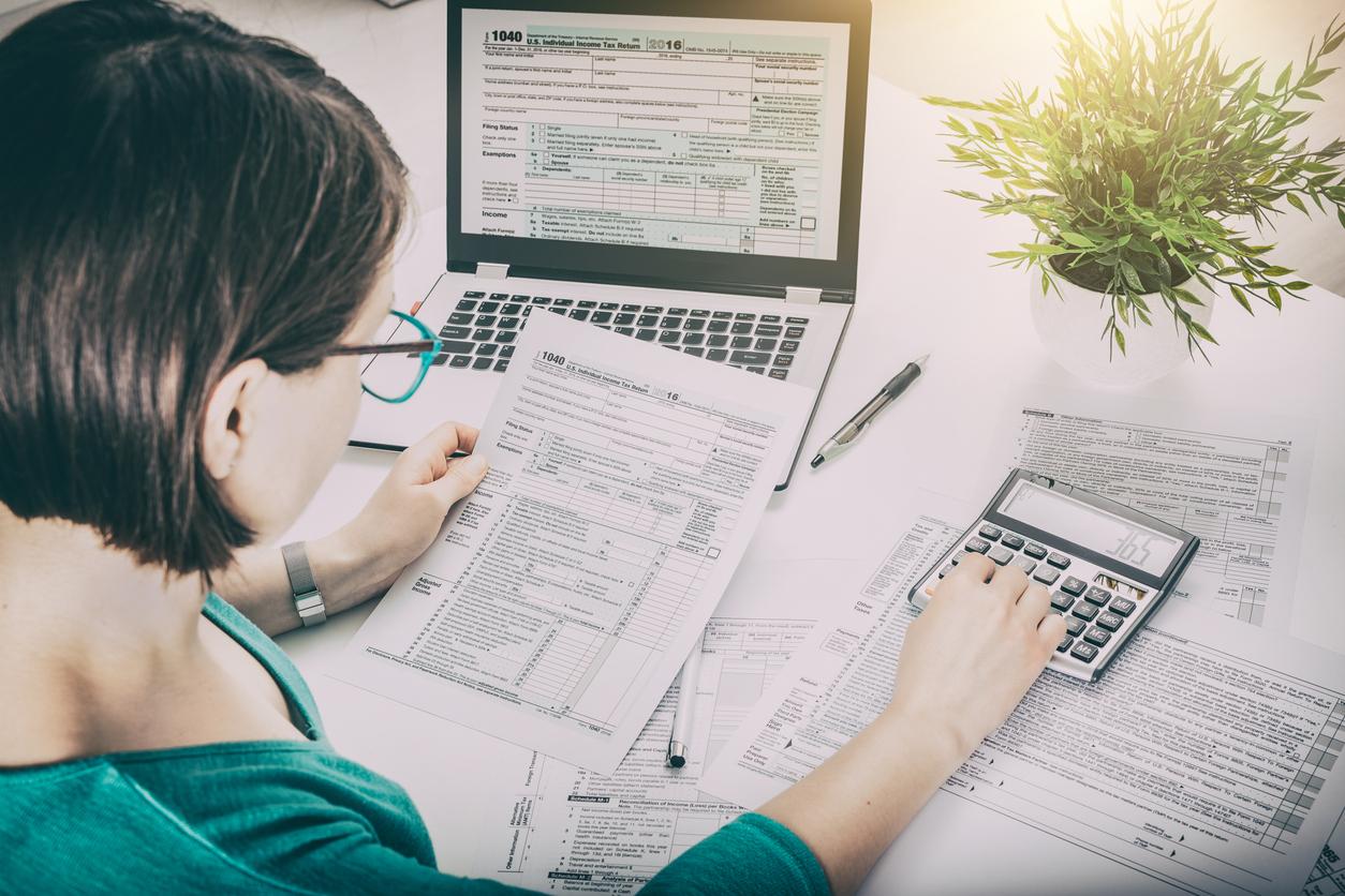 Mujer frente a computadora con calculadora y formularios del IRS, haciendo impuestos para su empresa unipersonal.
