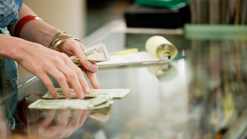 Shop keeper counting money in shop. concept: borrowing money