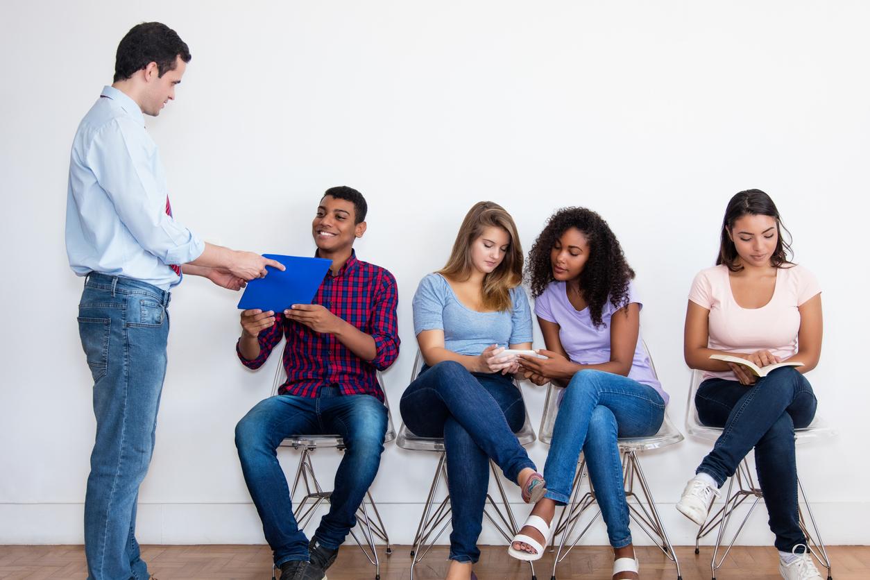 Jóvenes candidatos a un puesto de trabajo esperando su turno para una entrevista de trabajo. El dueño de la empresa está hablando con uno de los candidatos. Concepto: cómo contratar empleados.