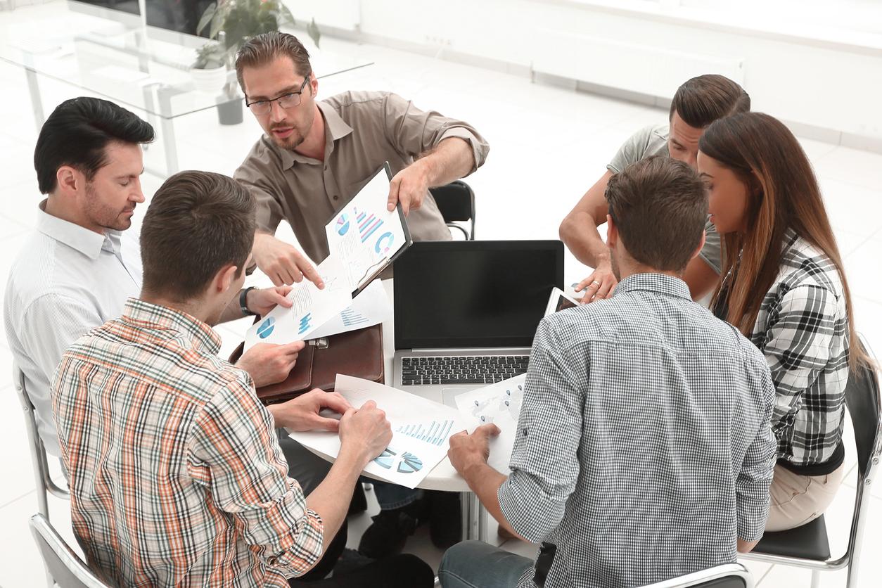 Seis miembros de una corporación alrededor de una mesa en una reunión de negocios. Concepto: Cómo declarar los impuestos en una Corporación