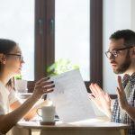 Dos compañeros de trabajo discutiendo en oficina sobre unos documentos. Cómo resolver conflictos entre tus empleados
