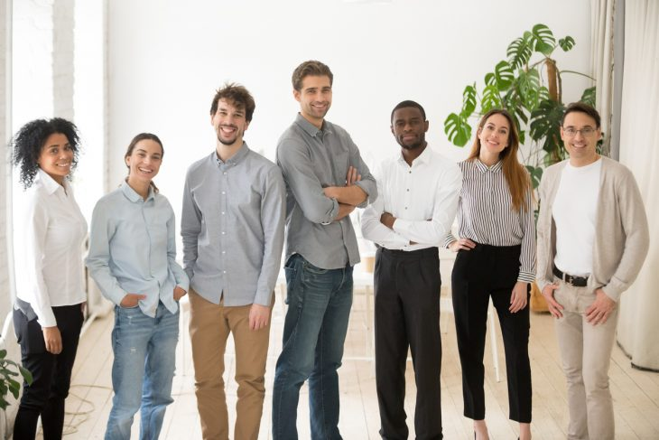 Young happy multiracial professionals or company staff looking at camera smiling. Concept: employees' salary