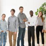 Retrato de grupo multiracial de jóvenes empleados de pie, sonriendo a cámara. Concepto: sueldo.