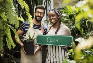 """Couple of business owners at flower shop holding an """"open"""" sign. Concept: how to change your business name."""
