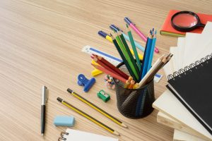 Multiple stationery items and office supplies on wood desk.