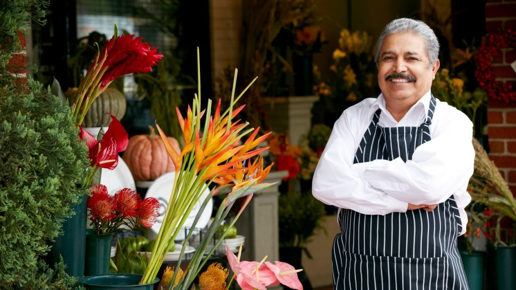 Portrait Of Male Florist Outside Shop Smiling To Camera. concept:undocumented immigrants