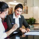 Representante de un banco reunida con una clienta revisando los documentos de un préstamo comercial. Concepto: Cómo elegir a un prestamista para tu empresa