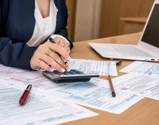 Woman torso on desk filling US tax form and using calculator. Concept: How to remove a tax lien