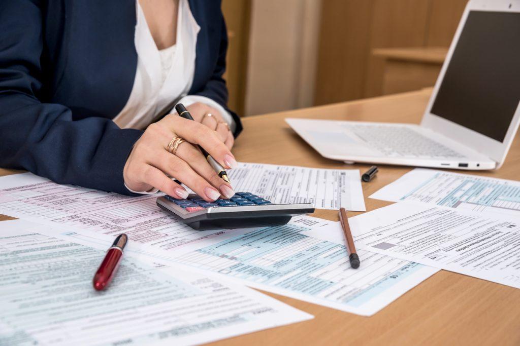 Torso de mujer sobre escritorio rellenando documentos sobre impuestos y usando calculadora. Concepto: cómo eliminar un gravamen fiscal