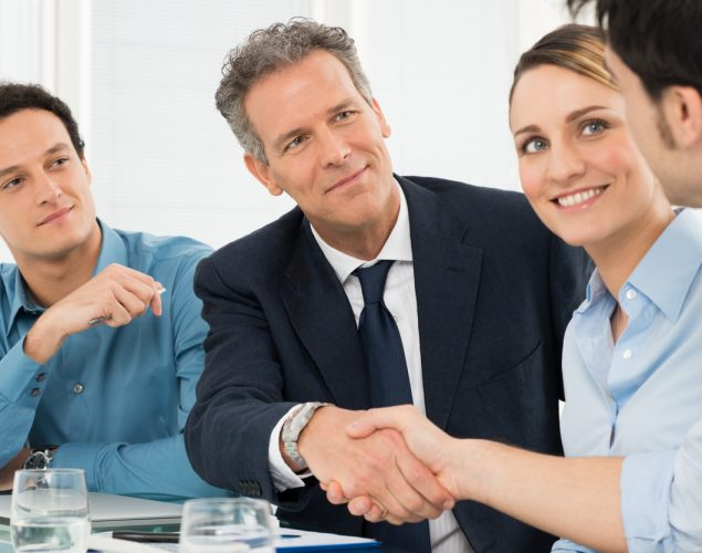 Two Successful Businessmen Shaking Hands In Front Of Their Colleague. Concept: supplier contracts