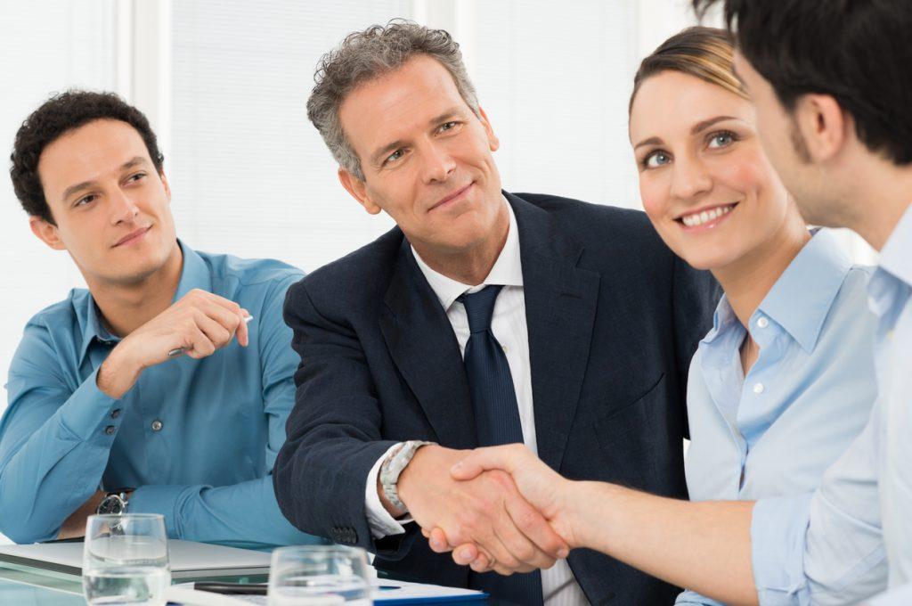 Hombre de negocios exitoso estrechando mano de dueño de pequeña empresa frente a su equipo. Concepto: contrato de proveedor