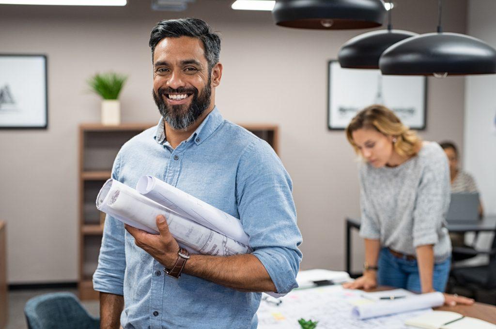 Arquitecto sonriente en su oficina sosteniendo rollos de planos. Concepto: contrato con el gobierno.