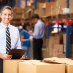 Manager In Warehouse Checking Boxes Smiling To Camera. Concept: self-motivated business owner.