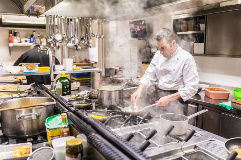 Chef in a restaurant kitchen cooking meat and mushrooms. Steam and vapor from the hob. Adult cook at work, wearing white uniform and black apron, focused on cooking. Concept: commercial kitchen equipment