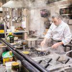 Chef cocinando en cocina industrial de restaurante. Concepto: equipos de cocinas industriales