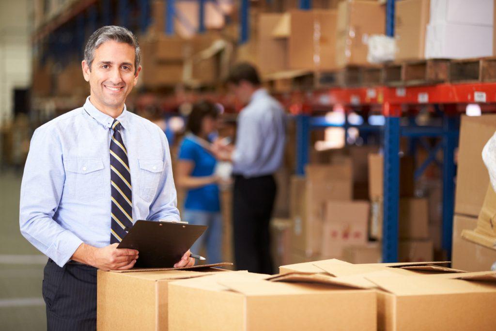 Gerente en almacén revisando paquetes. Concepto: motiivación