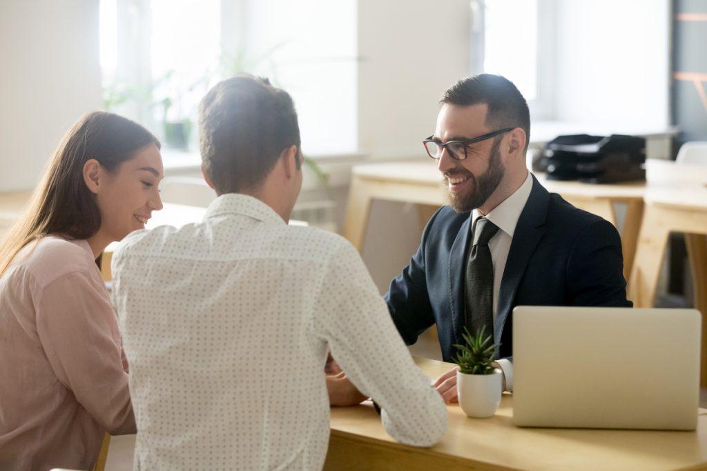 Banquero o prestamista en oficina asesorando a una joven pareja de clientes. Concepto: los mejores préstamos personales.