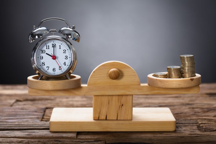 Closeup of clock and coins balancing on wooden weighing scale representing cash flow vs profit concept