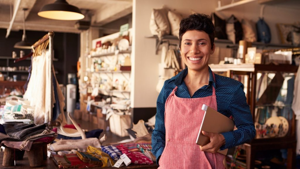 Portrait Of Female Owner Of Gift Store With Digital Tablet. concept: business names ideas