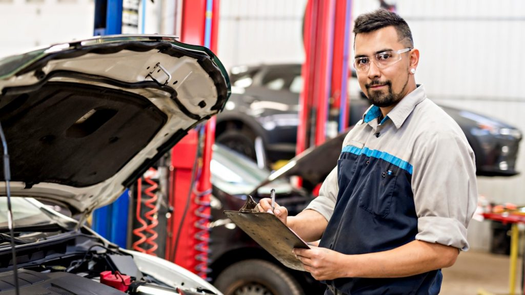 A Handsome mechanic job in uniform working on car. concept: business names ideas