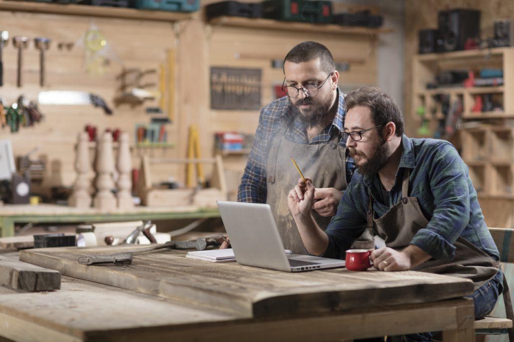 Dos dueños de taller de trabajo en madera revisando información en laptop. Concepto: Estado de flujo de efectivo