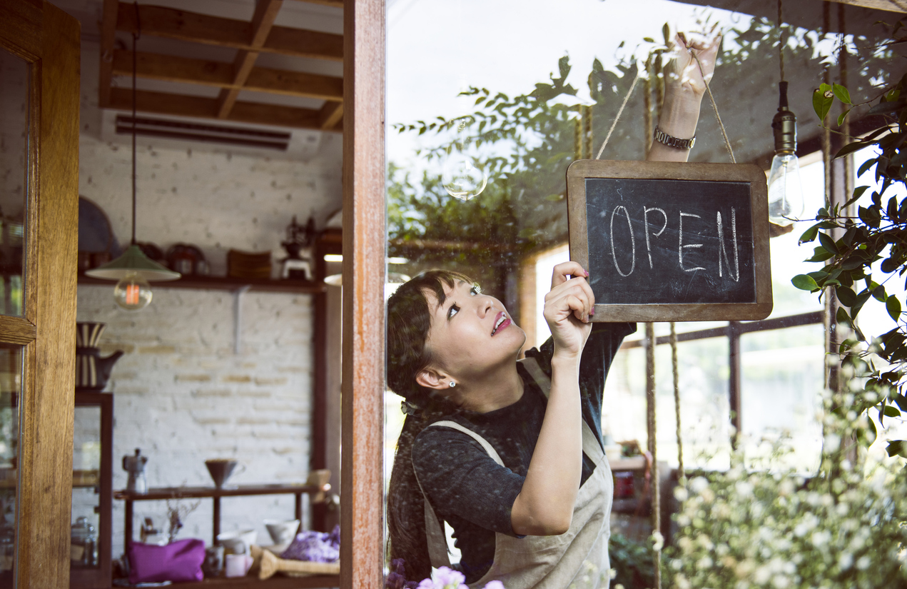 Young female entrepreneur hanging an open sign in small business. Concept: how to start a business with no money