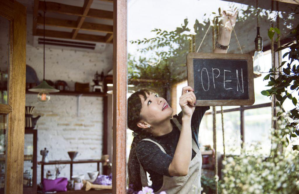 """Joven empresaria colgando cartel de """"abierto"""" en su negocio. Concepto: Cómo abrir un negocio sin dinero"""