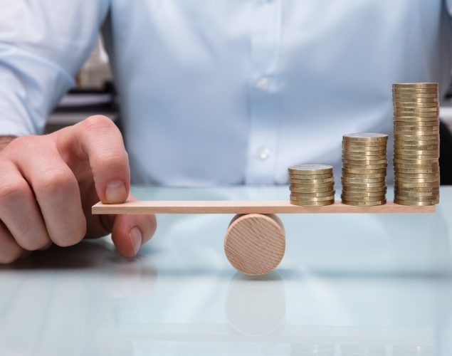 Close-up Of A Businessperson Balancing Increasing Stacked Coins With Finger On Seesaw. Concepto: How to convert profits into cash