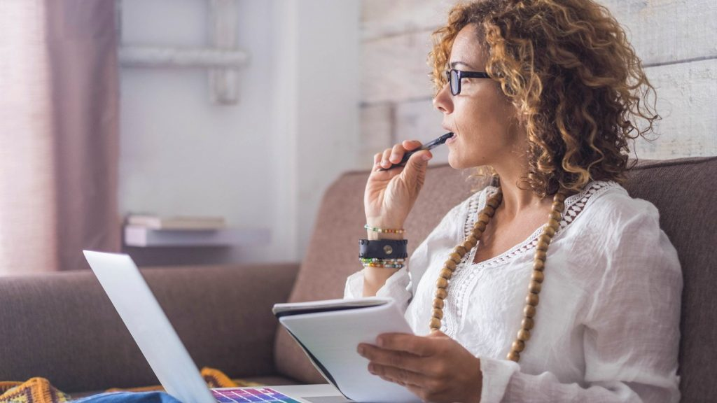 beautiful woman think and write notes on paper working on a laptop freedom from office at home. alternative lifestyle and place to work on. Nice life daily scene. concept: business letter