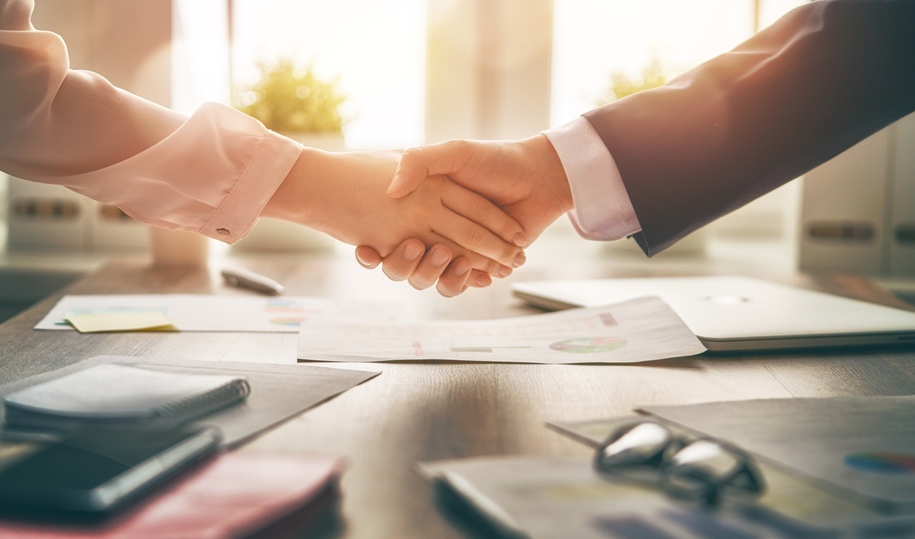 Two hands shaking in office, coming to an agreement. Concept: how to sell a business