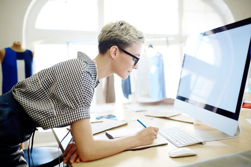 Young female clothing business owner working on computer. Concept: income statemet.