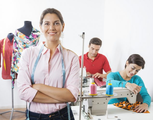 Portrait of smiling tailor with arms crossed standing at sewing factory with employees working in background. Concept: What's the difference between registering and incorporating a business?