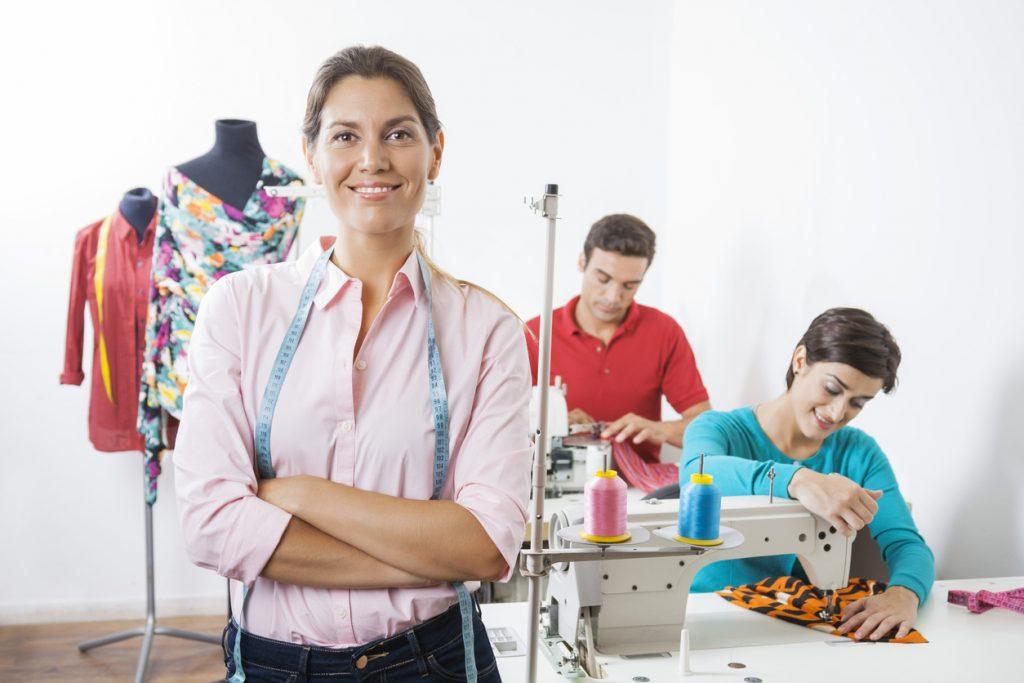 Dueña de negocio de confección de ropa en taller con trabajadores al fondo. Concepto:¿Qué diferencia hay entre registrar e incorporar un negocio?