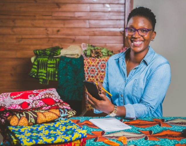African-American female fashion designer in her creative small business office, with different colored fabrics on the table. Concept: Creative small business ideas